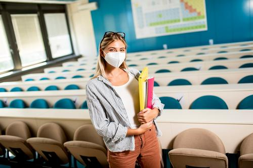 Female student wearing face protective medical mask for virus protection standing at lecture hall academic beautiful caucasian college concept corona