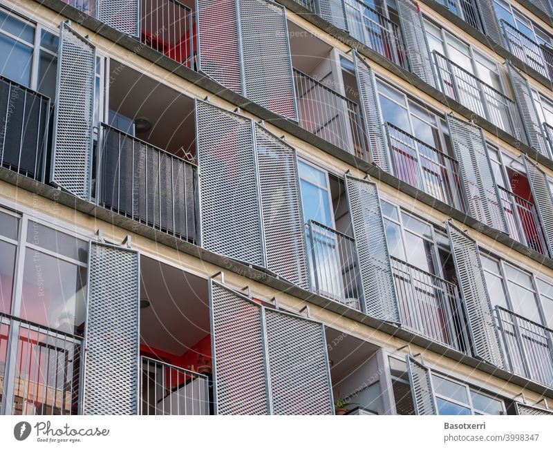 Detailed view of a modern residential building with balconies and hinged metal shutters Apartment Building dwell Modern High-rise Red Colour Glass Metal Load