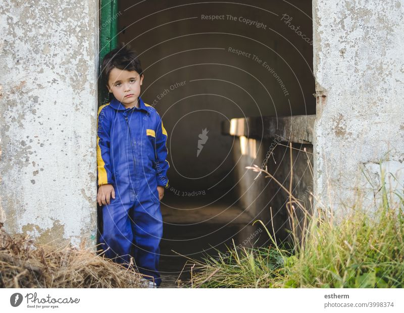 sad and pensive child next to a door childhood nostalgic thoughtful kid loneliness lonely expression freedom innocence unhappy portrait serious dream bored