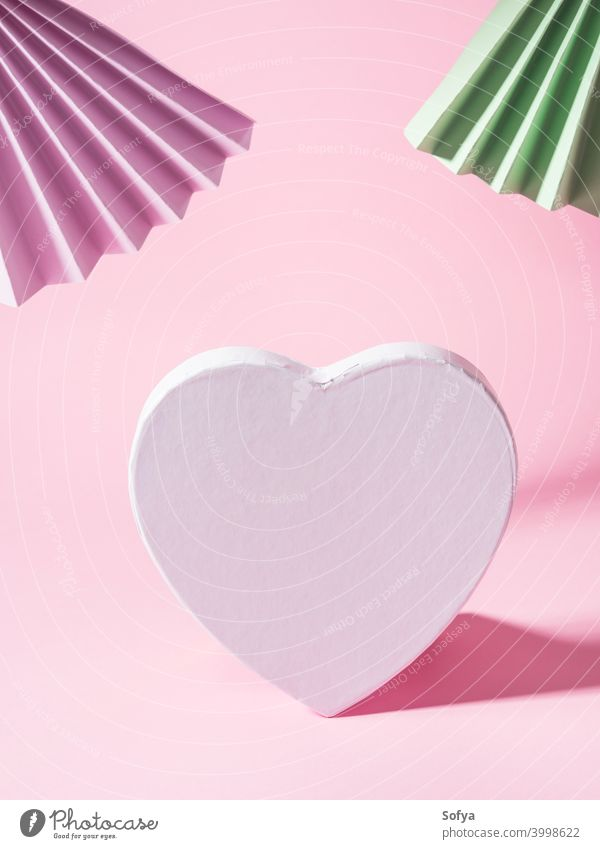 Geometrical pink background with paper fans and blank white heart shape love valentine day text invitation geometry holiday display bright mock up fashion