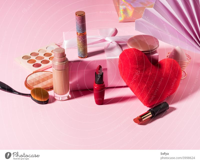 Cosmetics beauty background with red heart on pink makeup products cosmetic lipstick valentine foundation make up brush display shadow fashion geometry set day