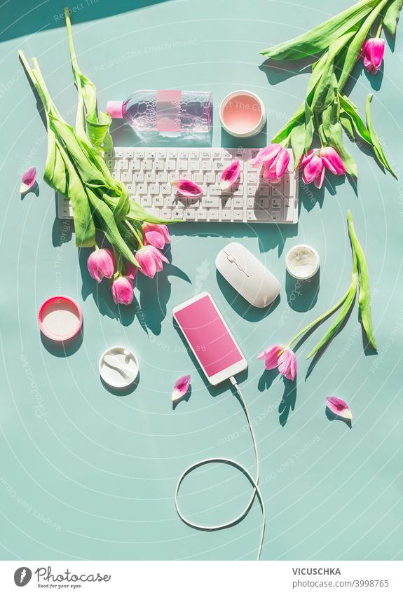 Female home office. Pastel blue desktop with PC keyboard , smartphone with blank screen and wire , cosmetics and pink tulips flowers in sunlight. Top view. Flat lay. Springtime. Blog layout