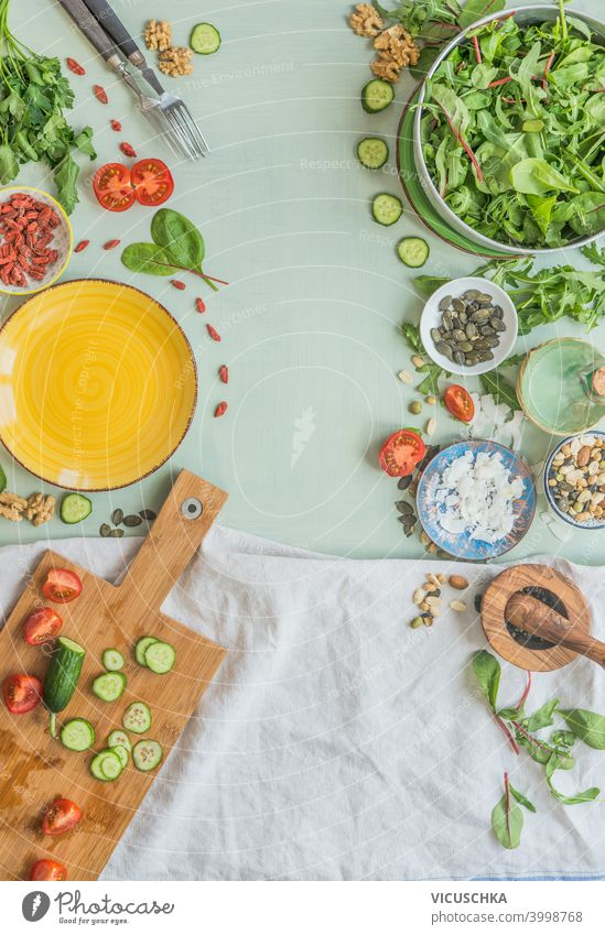 Various healthy salad ingredients on light green kitchen table background. Top view. Healthy lunch preparation, Frame various top view frame concept vegetarian