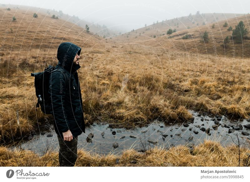 Young man exploring nature on a wet winter morning in the mountains adventure alone autumn backpack backpacker challenge cold exploration explore explorer fog