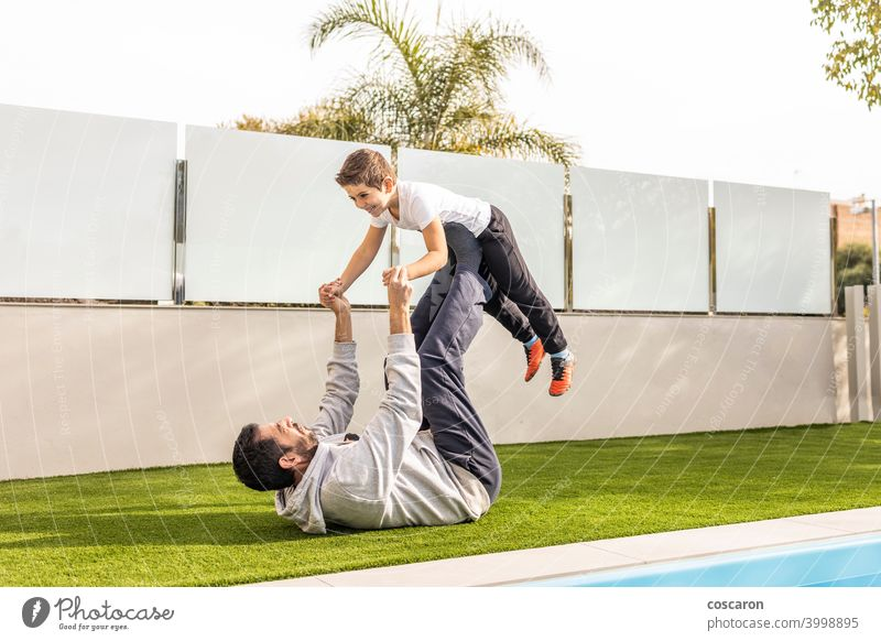 Father and son doing exercise in their home garden active activity balance balancing boy carefree carry cheerful child childhood children cute day family father
