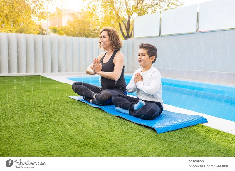 Mother and son doing yoga exercises in their home garden activity asia body calm child childhood cute family family yoga female fit girl grass gymnastics