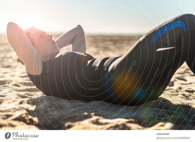 Middle aged woman doing exercise on the beach abs active adult alone athlete attractive balance beautiful blue body energy female fit fitness girl healthy