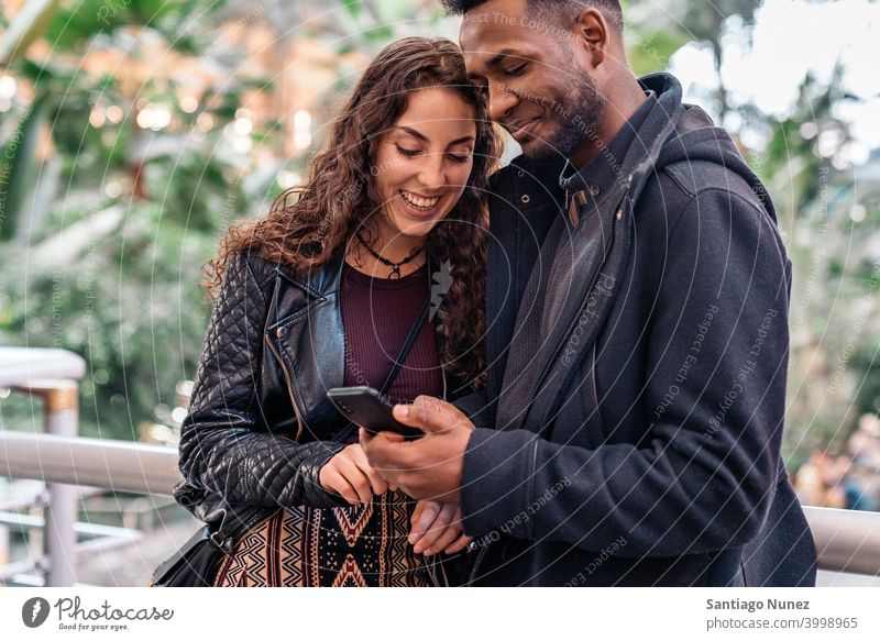 Happy Couple Using Phone couple relationship using phone interracial couple black afro african american cellphone diversity multi-racial black man ethnic
