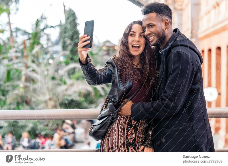 Love Couple taking a selfie couple relationship taking selfie front view interracial couple black man afro african american love cell cell phone cellphone city