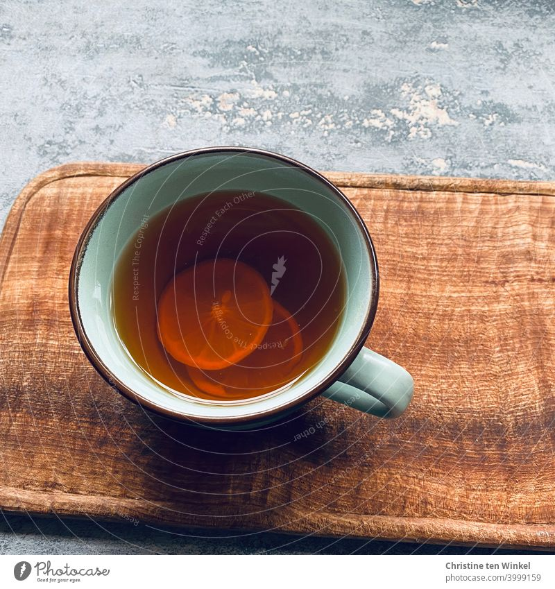 A cup of hot Darjeeling tea with lemon slices stands on a wooden board. Grey marbled background, shot from bird's eye view Tea Tea cup Darjeling Winter chill