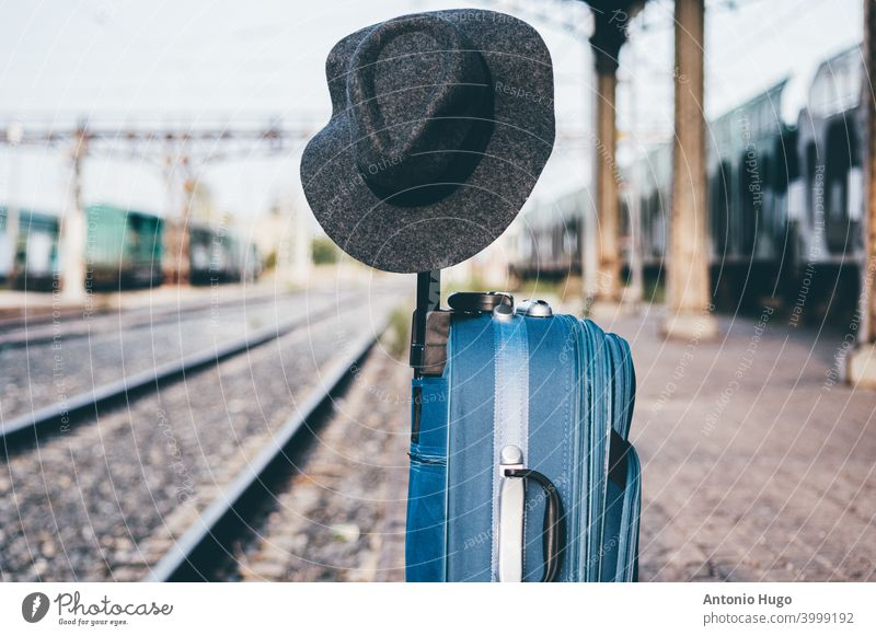 Hat perched on a suitcase at a train station. hat railroad baggage luggage journey transportation vacation concept departure waiting platform voyage leaving