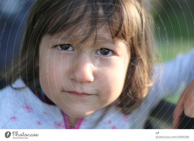 face of a beautiful child looking sceptical at the camera Dignity Inhibition Concern Longing Disappointment Exhaustion Reluctance Guilty Shame Fear Fatigue