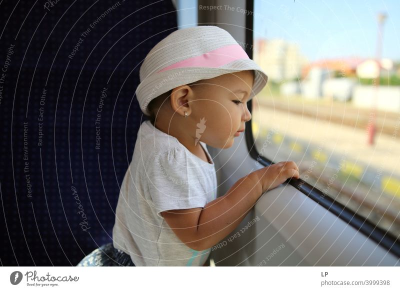 little girl wearing a hat looking outside a train window Looking away Upper body Contrast Light Copy Space bottom Structures and shapes Pattern Abstract