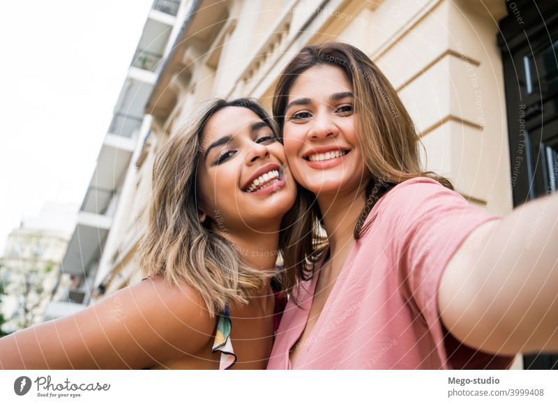 Two friends taking a selfie outdoors. young two woman city friendship laughing portrait fun tourism travel enjoyment smiling looking cute leisure media social