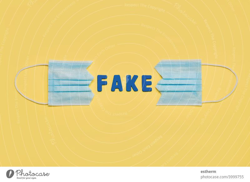 Protective surgical mask split in two with letters forming the word fake.Concept of protesting against coronavirus scams protective surgical mask