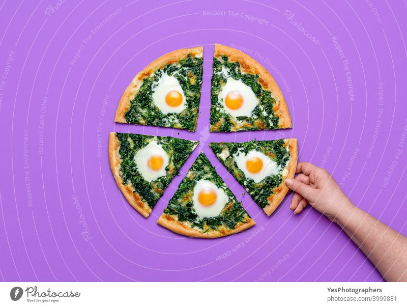 Sliced pizza with spinach and eggs. Woman taking a slice of pizza, flat lay Italian cheese colored background cuisine cut out delicious dinner directly above
