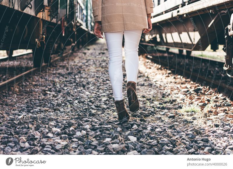 Woman's legs walking between two abandoned train carriages. woman wagon trains locomotive close up rear view railway tracks suitcase female girl lifestyle