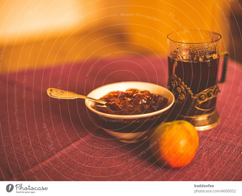 a still life with a tea glass in a metal saucer, next to it a porcelain bowl with apple jelly, in which a silver teaspoon is stuck, in front of both lies an apple. Everything stands on a rust-red tablecloth. Blurred foreground and background