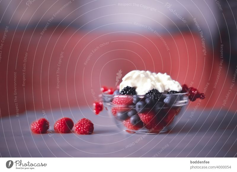 a glass bowl with fresh raspberries, blackberries blueberries and currants, on top in the <cup ripened yogurt. Three raspberries lie on the soft purple tablecloth. Blurred foreground and background