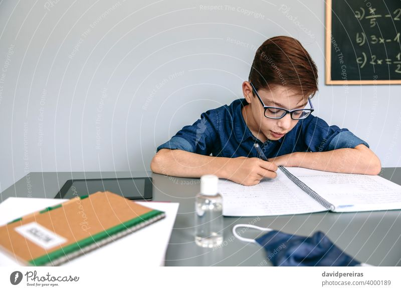 Boy writing in his notebook at school boy classroom mask on desk hand sanitizer coronavirus safety people student copy space education child epidemic no mask