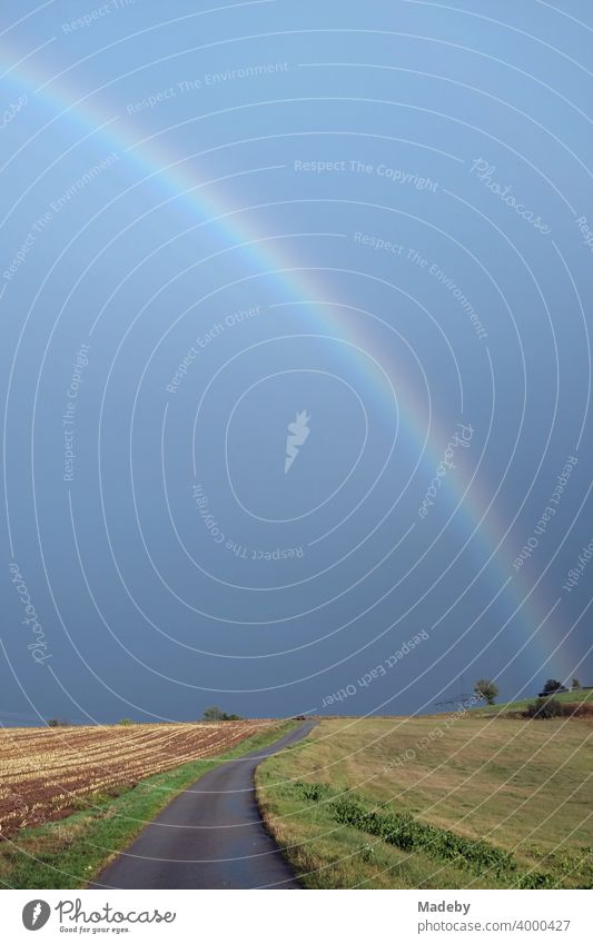 Road between meadows and fields with a rainbow in front of a dark sky on the horizon in autumn in Gembeck at Twistetal in the district of Waldeck-Frankenberg in northern Hesse
