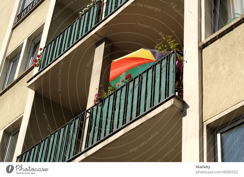 Colorful parasol on the balcony of a natural-colored tenement house in the style of the post-war period in the summer sunshine in Frankfurt am Main in Hesse, Germany