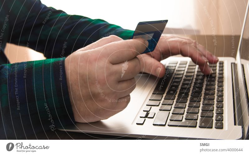 Close-up of a a hand holding a credit card in front of a laptop. Concept of card payment on the internet. adult banking bill buying checkout commerce computer