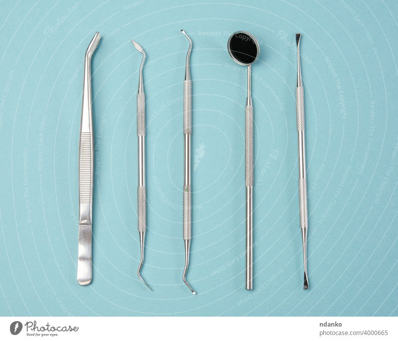 metal medical items of the dentist on a blue background teeth scraper equipment care mirror treatment clinic medicine stainless set dental professional