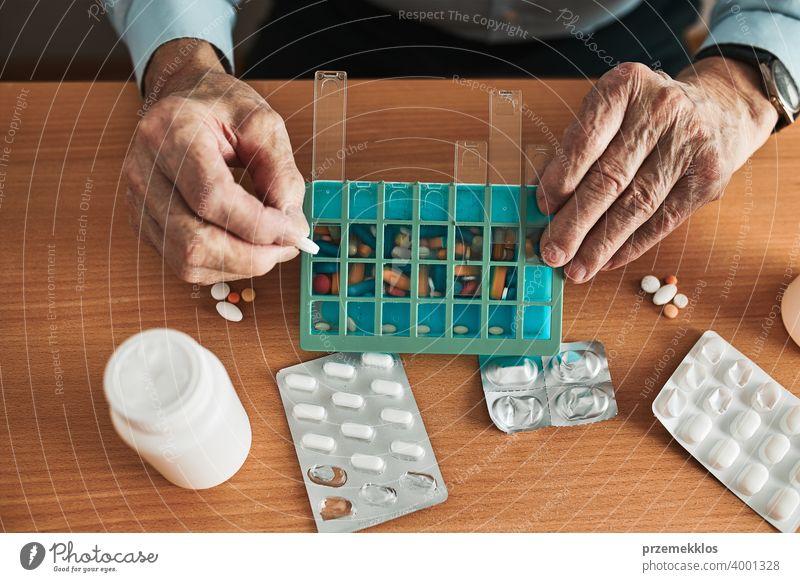 Senior man organizing his medication into pill dispenser. Senior man taking pills from box senior disease patient prescription medical medicine person