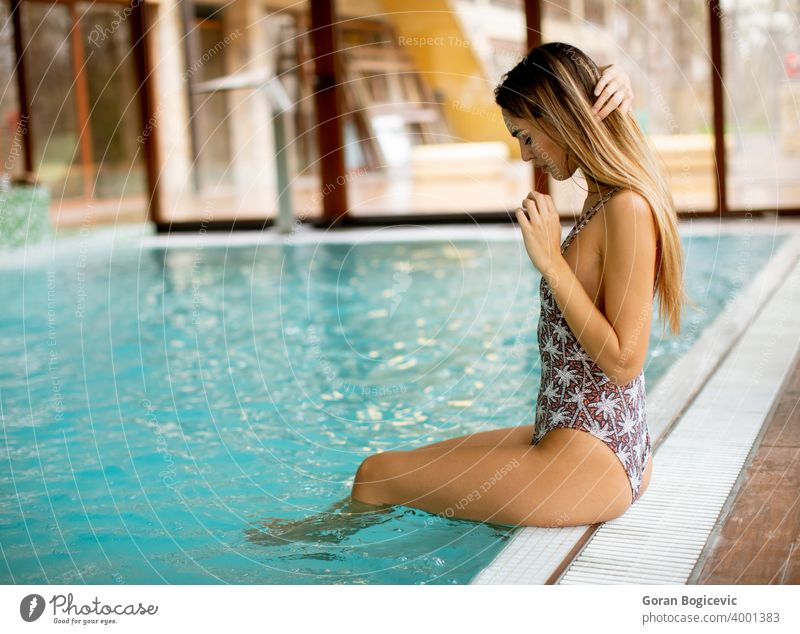 Beautiful young woman sitting by the swimming pool adult attractive beautiful beauty blue body caucasian cute day female fitness indoors leisure lifestyle model