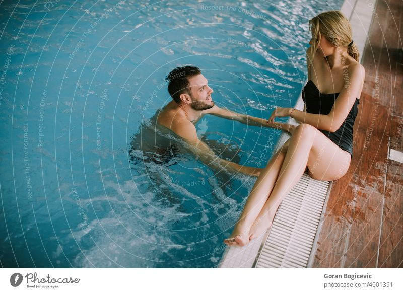 Young couple relaxing on the poolside of interior swimming pool 20s adult attractive beautiful beauty bikini caucasian cheerful cute edge enjoy enjoying