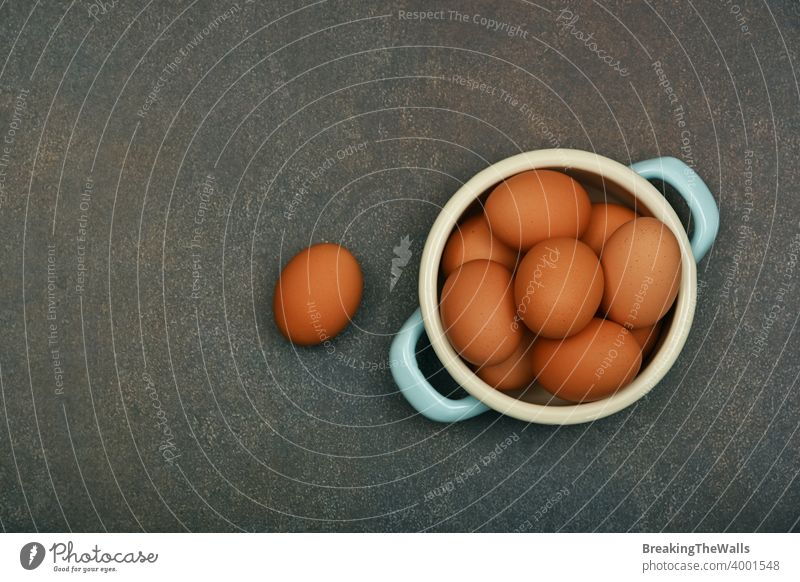 Bowl of brown chicken eggs on table Eggs fresh bowl pan pannikin metal group one many grunge dark closeup copy space food healthy natural eating cooking high