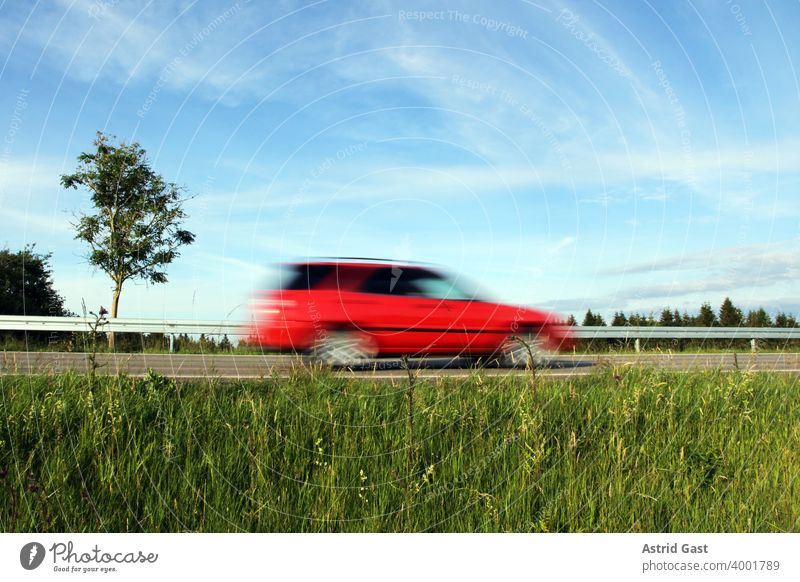 Speeding on German roads. A red car speeds along a road Driving Motoring Street Lawn Leadfoot swift quick fast and furious Germany Car Vehicle Transport