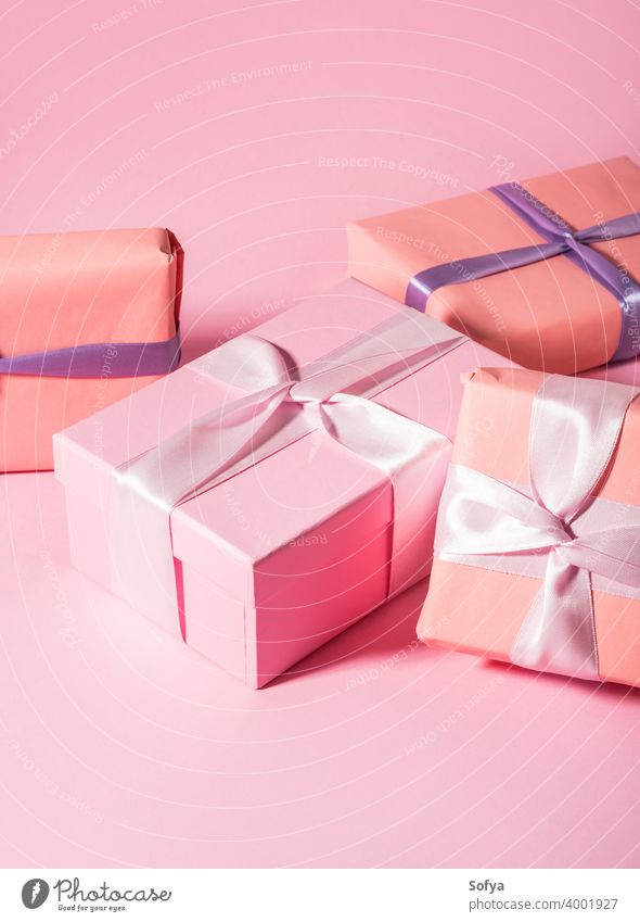 Pink wrapped gift boxes with ribbons on monochrome background baby shower pink valentine day mother birthday anniversary pastel satin present minimal stack