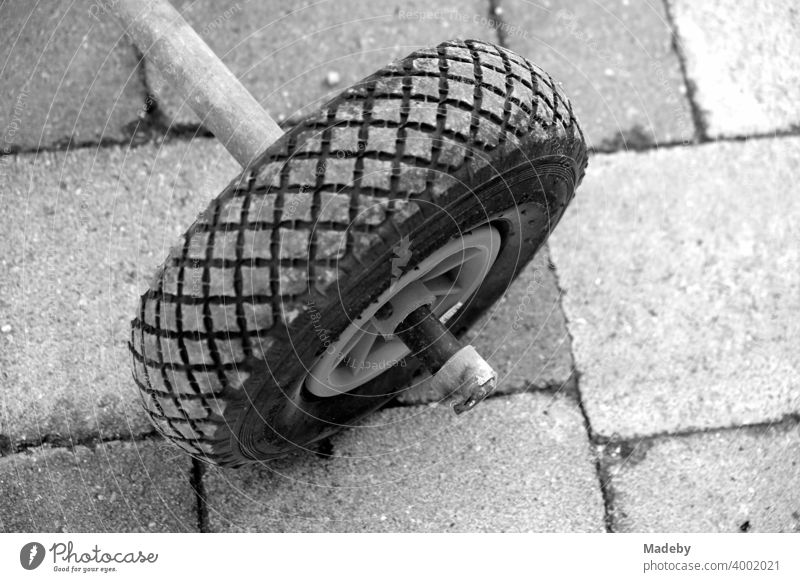 Wheel of an old sack barrow on a self-made tricycle on a farm in Rudersau near Rottenbuch in the district Weilheim-Schongau in Upper Bavaria, photographed in classic black and white