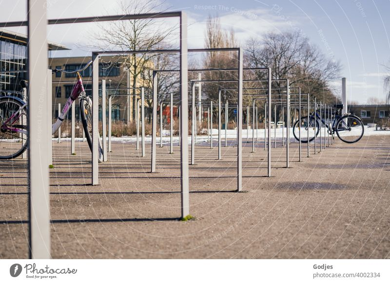 Bicycle stand in a public place with two bicycles Bicycle rack Cycling Exterior shot Parking Deserted Means of transport Colour photo Transport Town Day