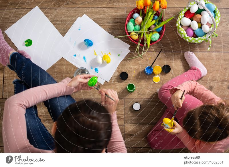 A mother and her daughter painting Easter eggs baby basket blonde bunny celebration childhood colors creativity decoration easter family girl happiness holiday