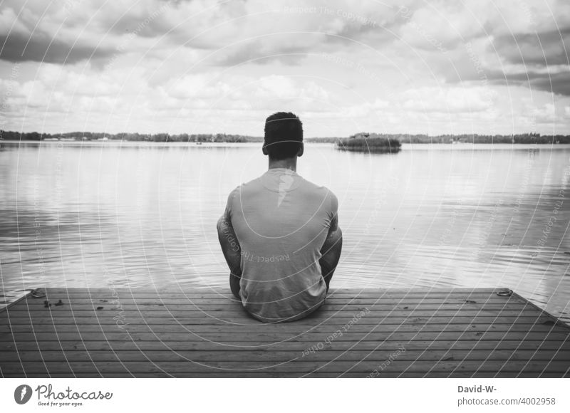 Man sits lonely and alone on a jetty at the lake and enjoys the silence tranquillity Relaxation silent Footbridge Lake gap Meditative Sit To enjoy Loneliness