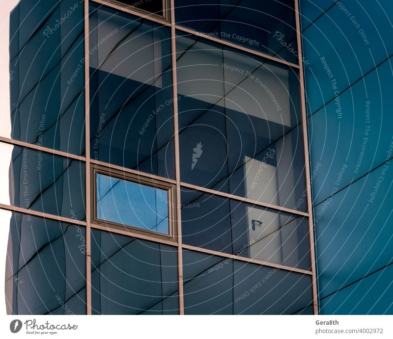 mirrored windows of the facade of an office building with blue panels and yellow window frames abstract architecture background blue walls building facade