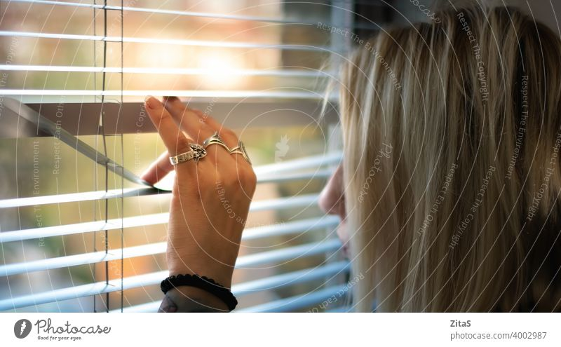 Blonde woman peeking through the window blinds blonde looking curious interior person hand life day shutters thinking spy privacy