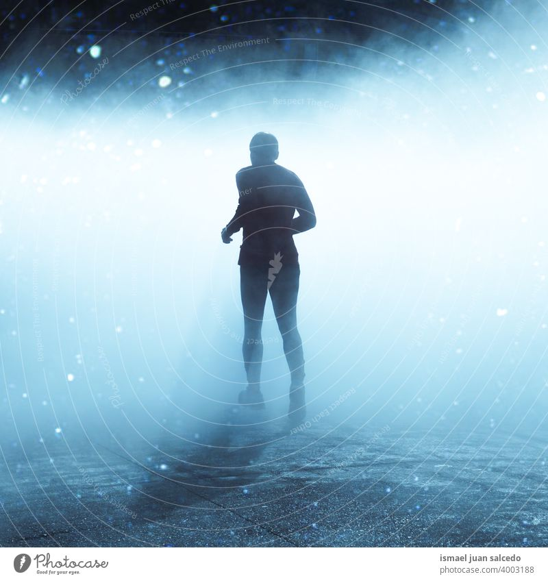man running on the street in foggy days in winter season one person marathon runner jogging action fitness health lifestyle jogger sport exercise athletic speed