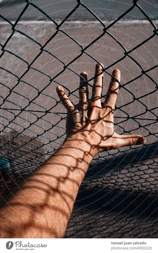metallic fence shadows on the man hand arm body part skin shapes fingers palm wrist steel street outdoors grabbing gesturing concept reaching feeling life style