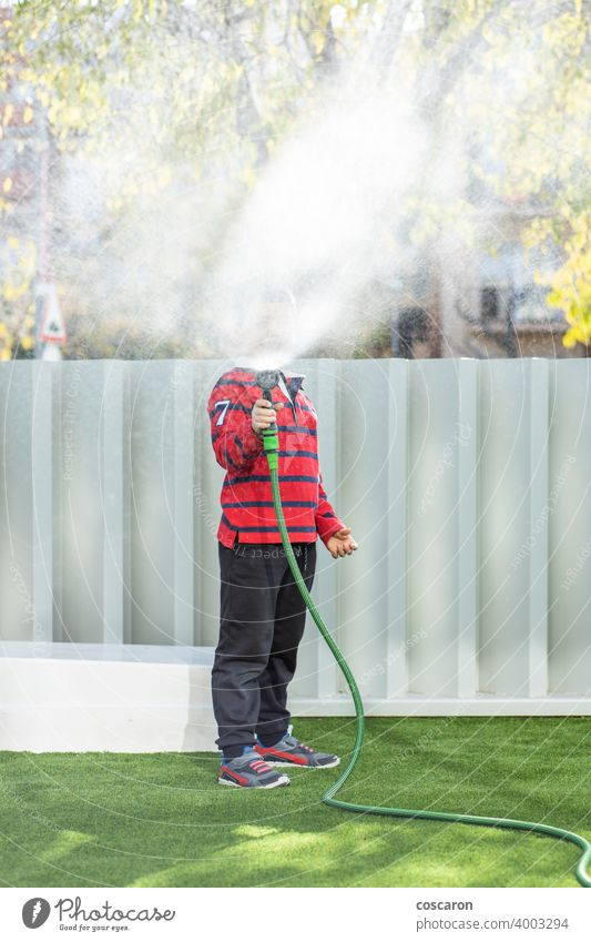 Little boy watering the grass in the garden action activity child childhood children drops enjoy family fountain fresh fun gardening green happiness happy hose