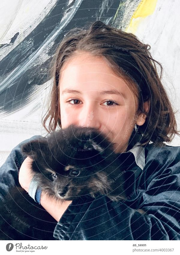 Girl carries Black Pomeranian puppies Pygmy Spitz breed of dog Looking into the camera Joy Love of animals Colour photo 1 Animal Pet Day Dog Cute Friendliness