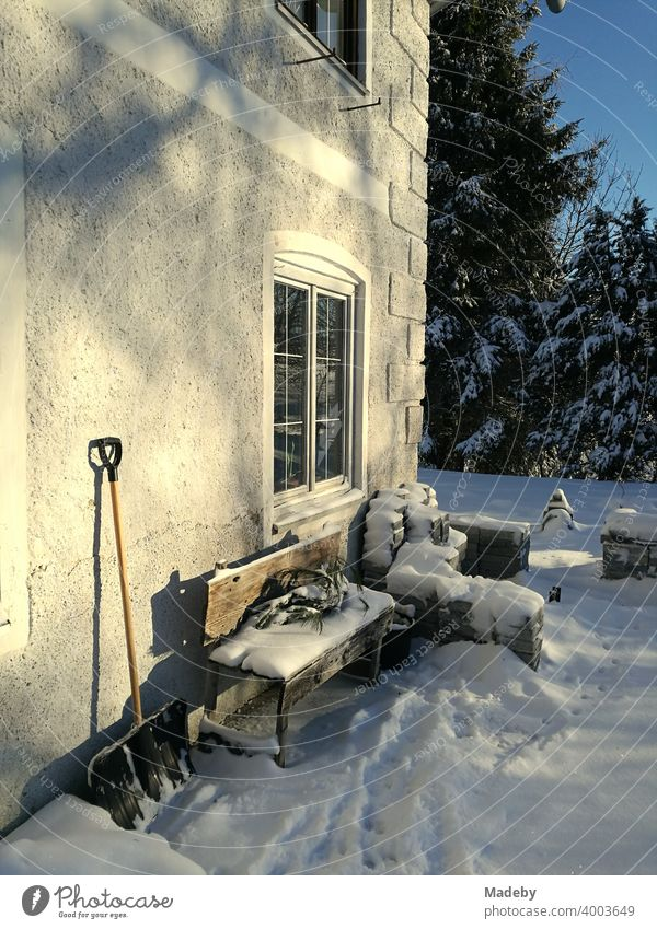 Snow-covered wooden bench and leaning snow shovel at an old farmhouse in winter at sunshine in romantic snowy landscape in Rudersau near Rottenbuch in the district Weilheim-Schongau in Upper Bavaria