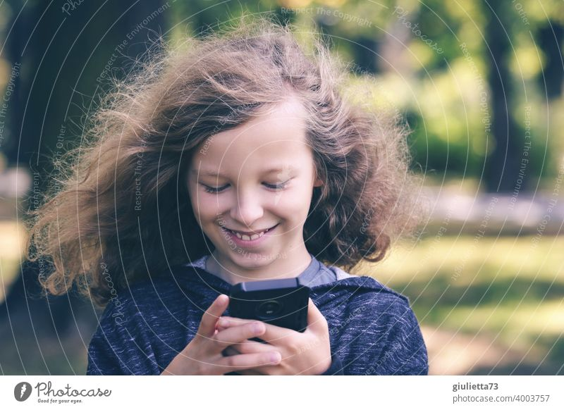 Portrait of happy boy with long hair reading funny messages on his mobile phone Front view Upper body portrait Central perspective Downward