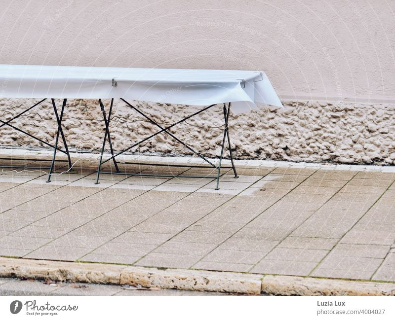 An empty table on the sidewalk waits in vain for guests.... Table Empty forsake sb./sth. tablecloth White Town Loneliness Wait nobody Street urban Deserted