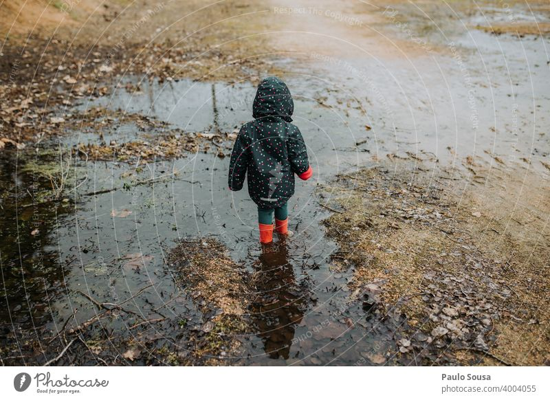 Child with red rubber boots playing on a puddle Rubber boots Red childhood Girl Water Human being Boots Playing Rain Puddle Dirty Day Copy Space bottom Toddler