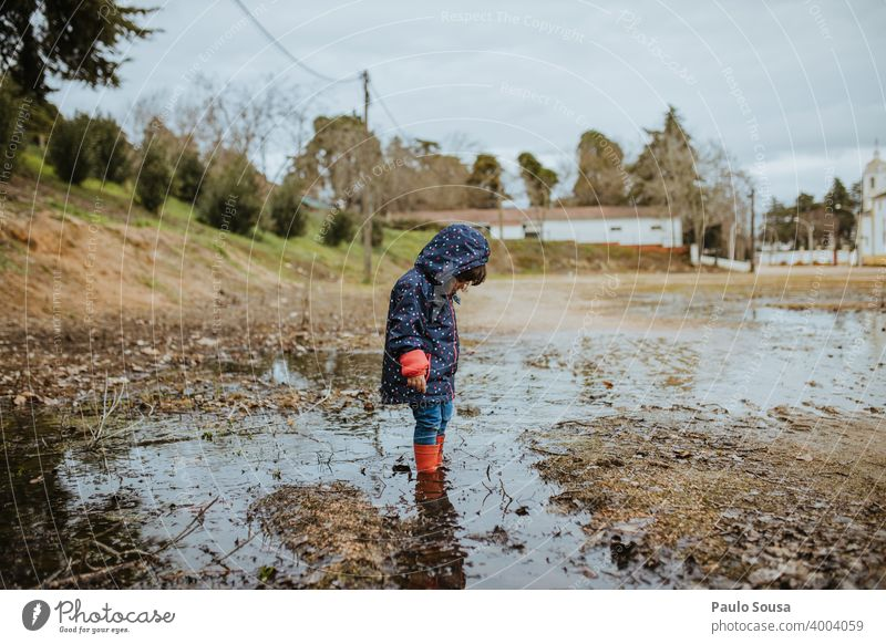Child with red rubber boots playing on a puddle childhood Puddle Rain Authentic Human being Playing Rubber boots Water Wet Exterior shot Joy Colour photo