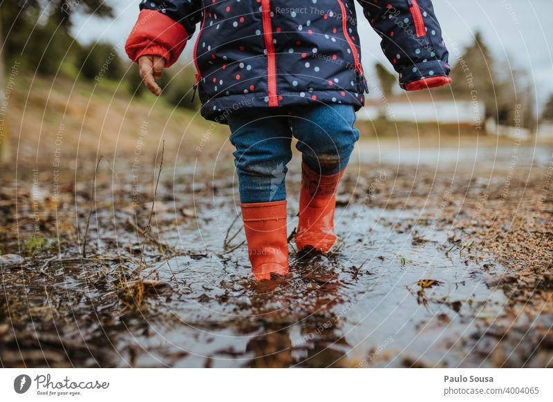 Child with red rubber boots playing on a puddle Rubber boots Red childhood Exterior shot Water Playing Weather Bad weather Dirty Boots Colour photo Day Joy